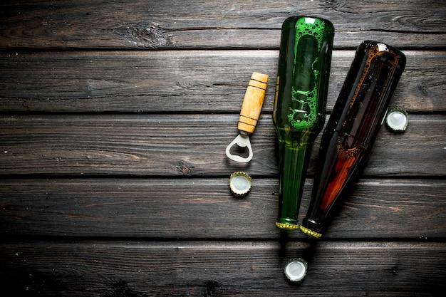 Bier in glasflaschen und öffner. auf holztisch