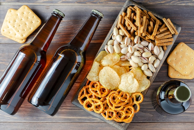 Bier in glasflaschen und salzige snacks für bier in holzgeschirr. rustikaler stil. brauner hölzerner hintergrund.