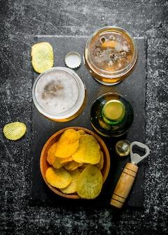 Bier mit pommes und öffner auf dem schneidebrett. auf schwarzem rustikalem tisch