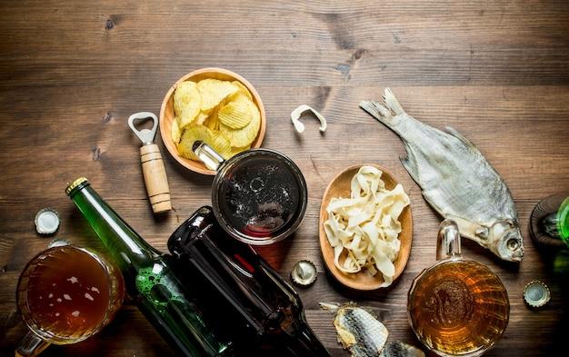 Bier mit pommes und tintenfischringen in schüssel und getrocknetem fisch. auf holztisch