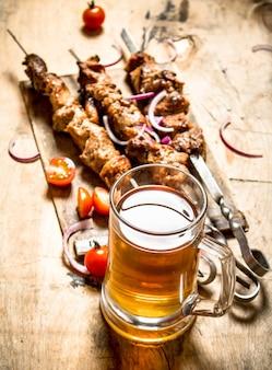 Bier mit schweinefleisch shish kebab und tomaten.