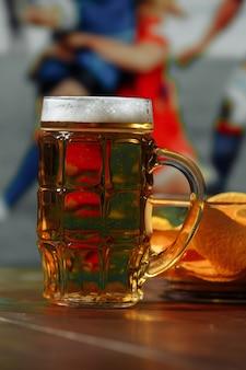 Bier mit snack auf holztisch gegen fußballfeldhintergrundsport- und unterhaltungskonzept vertikales bild
