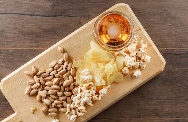 Bier mit snack in einem becherglas auf holz- und schneidebretttisch, draufsicht.