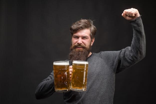 Bier. oktoberfest. gut aussehender mann, der bier aus glas trinkt. lächelnder bärtiger hipster, der craft beer trinkt. brauen. stilvoller typ im pub. bierkneipe.