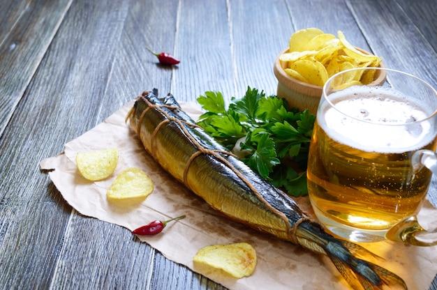 Bier snacks. geräucherter fisch, pommes, ein glas lagerbier auf einem holztisch.