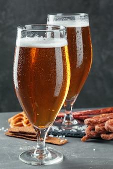 Bier und appetitliche biersnacks eingestellt. tisch mit krug bier, holzbrett mit würstchen
