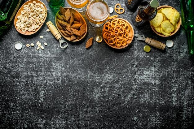 Bier und eine auswahl verschiedener snacks mit öffnern. auf schwarzem rustikalem hintergrund