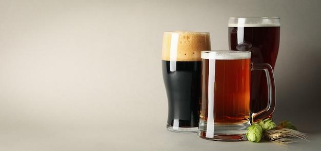 Bier und grüner hopfen auf grauem tisch