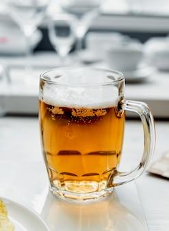 Bier und pommes auf dem großen weißen tisch