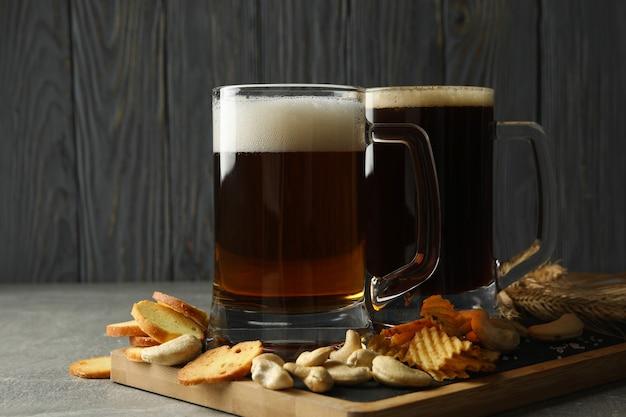 Bier und snacks auf grauem tisch gegen holz