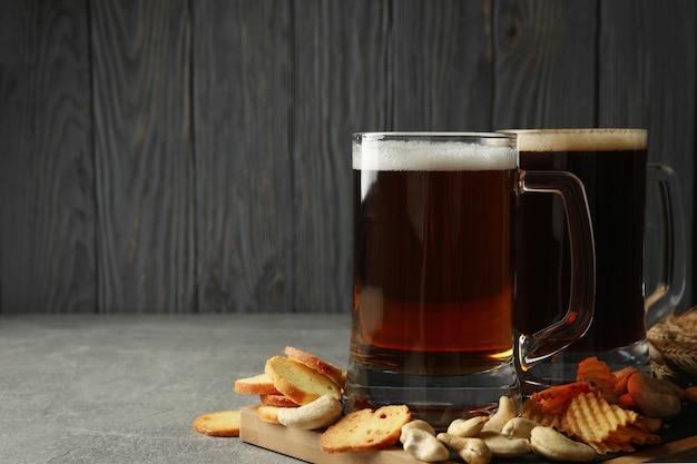 Bier und snacks auf grauem tisch gegen holzwand