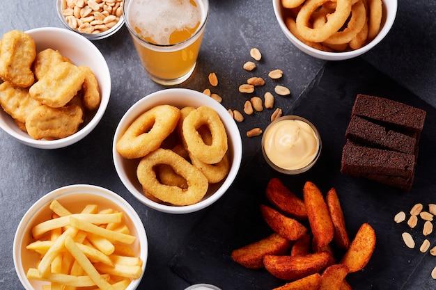 Bier und snacks auf steintisch. nüsse, pommes. ansicht von oben.