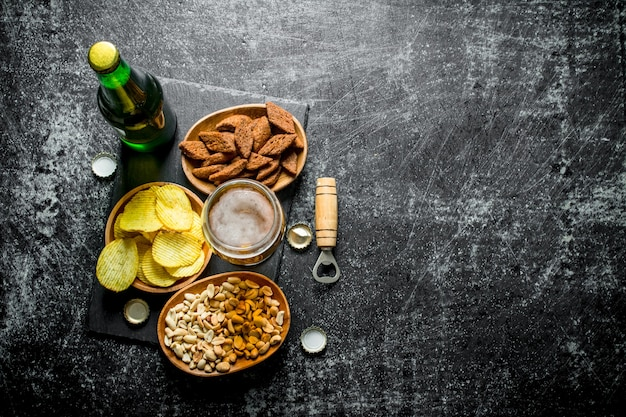 Bier und verschiedene arten von snacks in den schalen. auf schwarzem rustikalem hintergrund