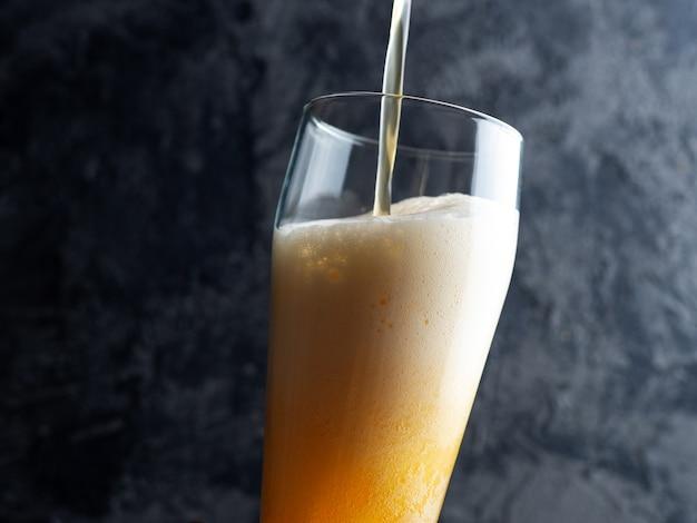 Bier wird in ein glas auf einem dunklen hintergrund gegossen