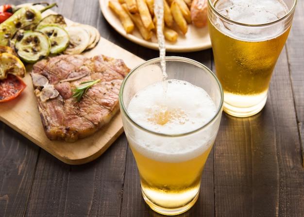 Bier wird in glas mit gourmet-steak und pommes frites auf hölzernem hintergrund gegossen