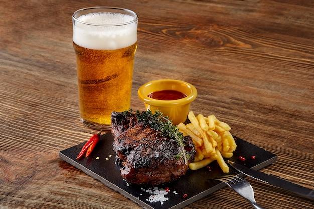 Bier wird in glas mit gourmet-steak und pommes frites auf holzhintergrund gegossen