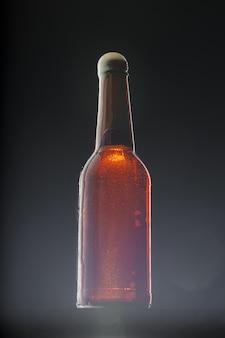 Bierflasche auf dunklem hintergrund, kopienraum