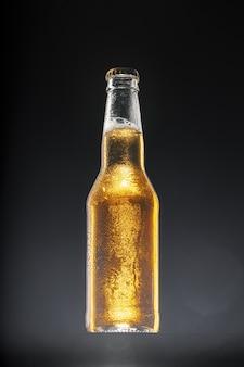 Bierflasche gegen dunklen schwarzen hintergrund