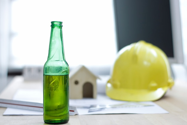 Bierflasche im büro am schreibtischingenieur