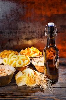 Bierflasche in der nähe von tellern mit pistazien, nüssen und anderen leckeren snacks, weizen und verstreuten pommes auf dunklem holzschreibtisch. lebensmittel- und getränkekonzept