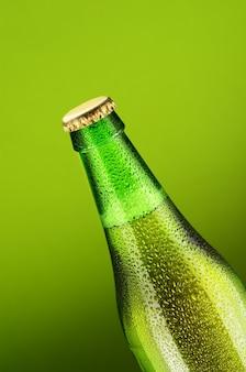 Bierflasche mit wassertropfen auf einem grünen hintergrund