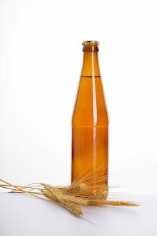 Bierflasche und gerste lokalisiert auf weißer wand.