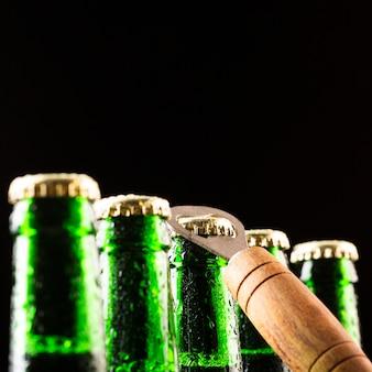 Bierflaschen, die auf einer reihe und einem öffner stehen