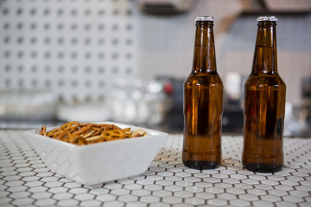 Bierflaschen und eine schüssel mit snacks auf der bartheke