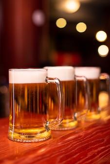 Biergläser in einer reihe stehen an der bartheke in der kneipe