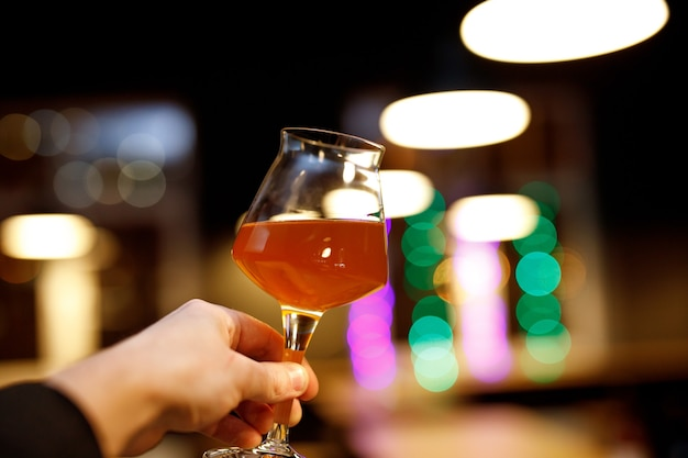 Bierglas mit einem dünnen bein in der hand.