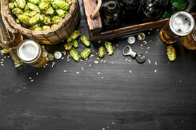 Bierhintergrund. frisches bier und zutaten. auf der schwarzen tafel.