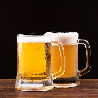 Bierkrüge mit schaum auf hölzernem brett