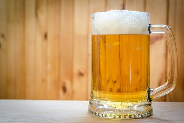 Bierkrug auf dem hölzernen hintergrund