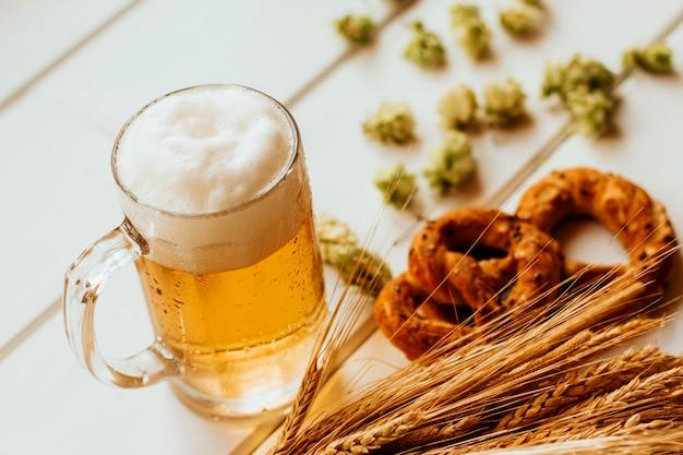 Bierkrug, hopfenzapfen, ährchen roggen und weizen und brezeln auf weißem holz