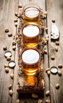 Bierparty. drei biere auf birke stehen mit pistazien herum.