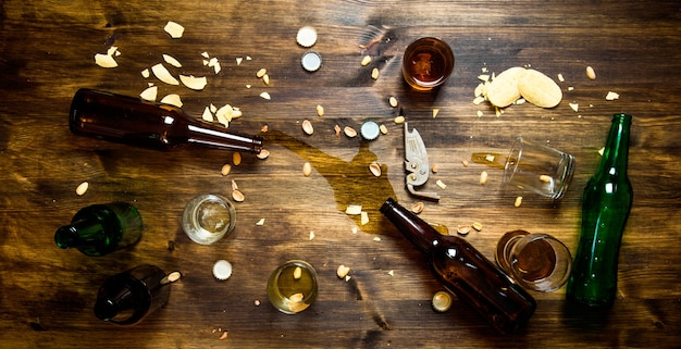 Bierparty. verschüttetes bier, flaschenverschlüsse und übrig gebliebene pommes auf dem tisch. draufsicht
