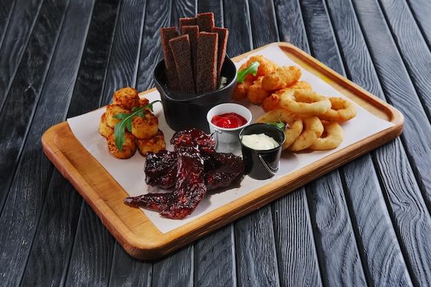 Biersnack. buffalo chicken wings, frittierzwiebeln, kartoffeln, toastbrot, sauce und käse