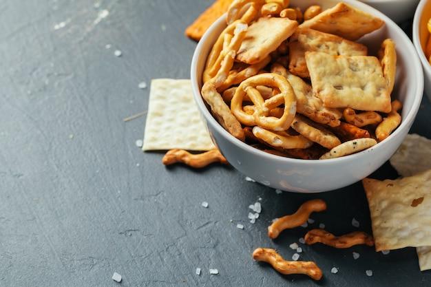 Biersnacks auf steintisch. verschiedene cracker, kartoffelchips. ansicht von oben