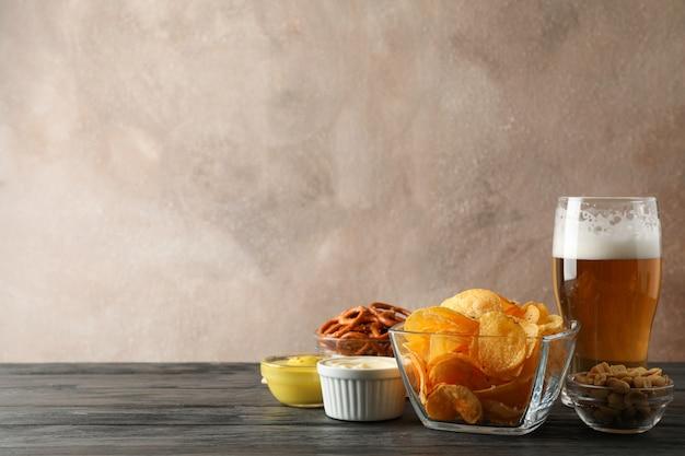 Biersnacks, glas bier, kartoffelchips, biernüsse, saucen, glas bier auf holz, platz für text