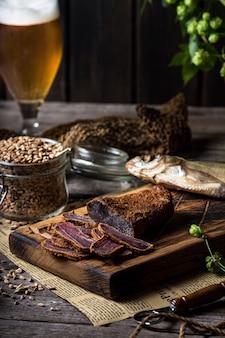 Bierstillleben mit fischen und flaschen. fleisch basturma. oktoberfest. trockener fisch und trockenes fleisch. land mahlzeit