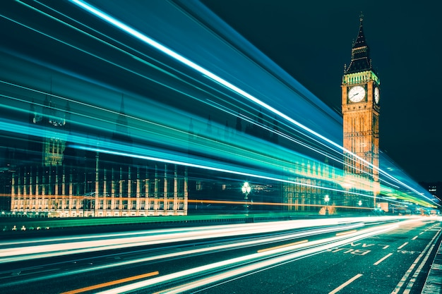 Big ben, eines der bekanntesten symbole sowohl in london als auch in england, wird nachts zusammen mit den lichtern der vorbeifahrenden autos gezeigt