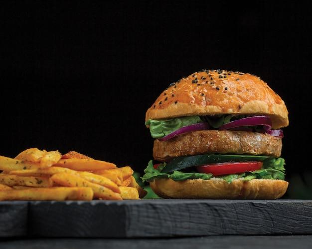 Big mac burger und kartoffelsticks auf einem dunklen holzbrett.