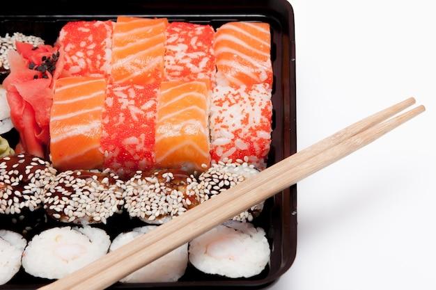 Big sushi set ib schwarze plastikbox auf weißem hintergrund, draufsicht nahaufnahme, kopienraum.