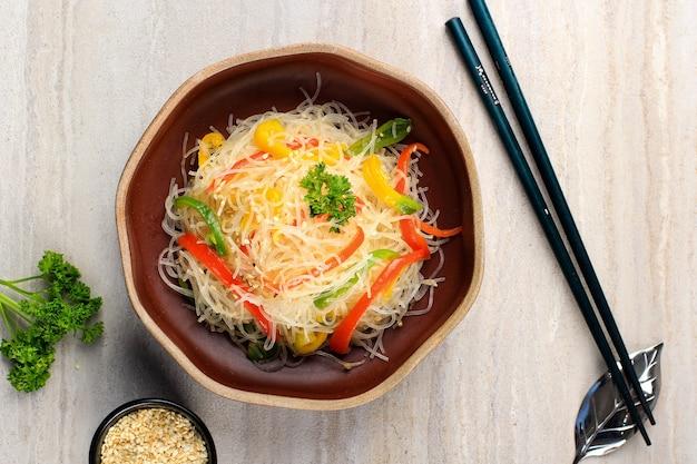 Bihun goreng oder stir fry vermicelli (glasnudeln) oder japchae mit geschnittenem paprika. serviert auf keramikschale mit stäbchen. platz für text kopieren