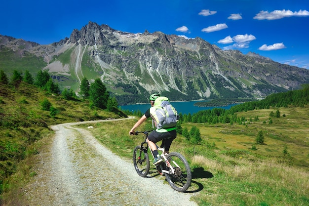 Biker auf bergschotterstraße in der schönen landschaft der berge