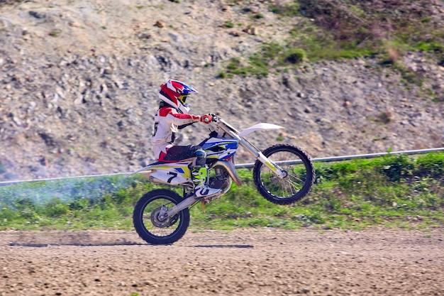 Biker auf motorrad stunts während der fahrt auf der hinterradseitenansicht