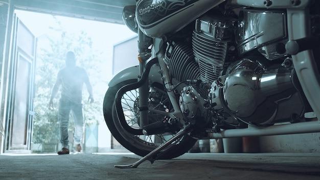 Biker betritt die garage und geht zum chopper