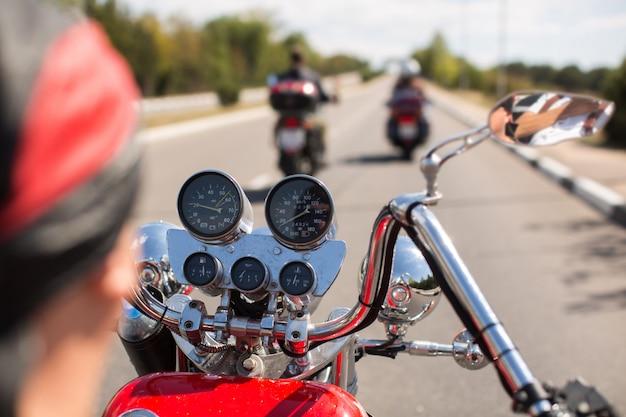 Biker, der motorrad auf straße am morgen sonnigen tag reitet. von hinten geschossen