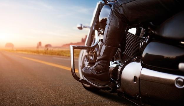 Biker fährt auf klassischem chopper, blick vom hinterrad. weinlesefahrradfahrer auf motorrad, straßenabenteuer im wüstental auf sonnenuntergang, freiheitslebensstil