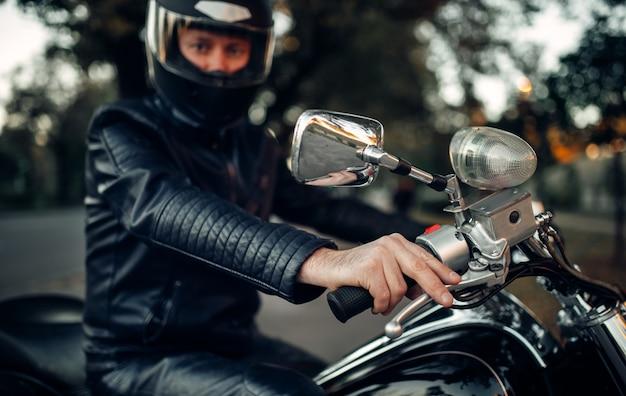 Biker im helm posiert auf einem motorrad, klassischer hubschrauber. vintage fahrrad, fahrer und sein zweirädriger freund, freiheit lebensstil, radfahren